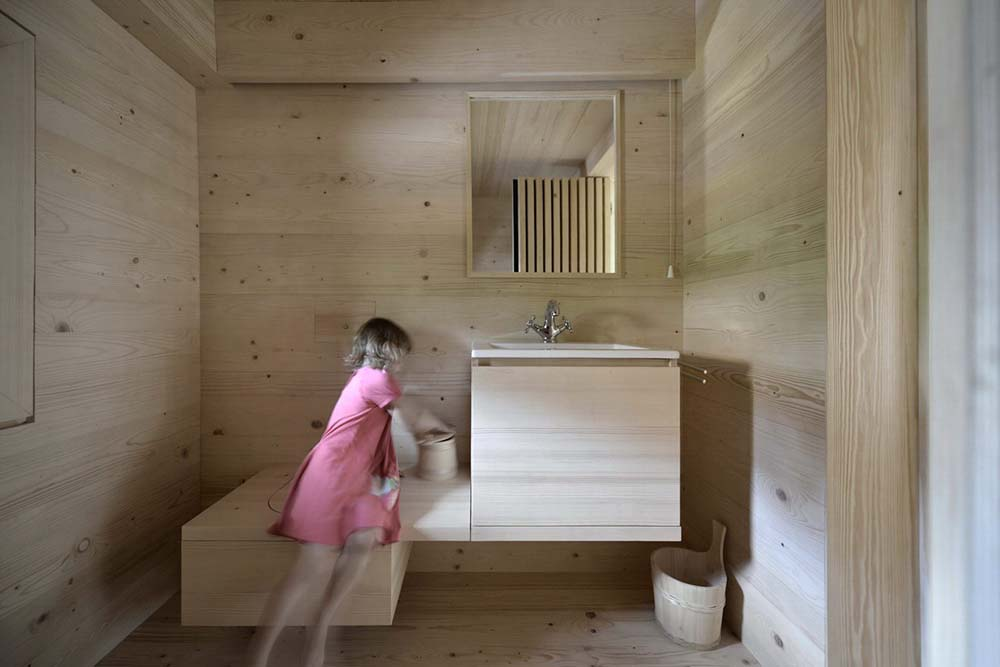 The toilet and the vanity are designed as one wooden structure that pairs with the walls.