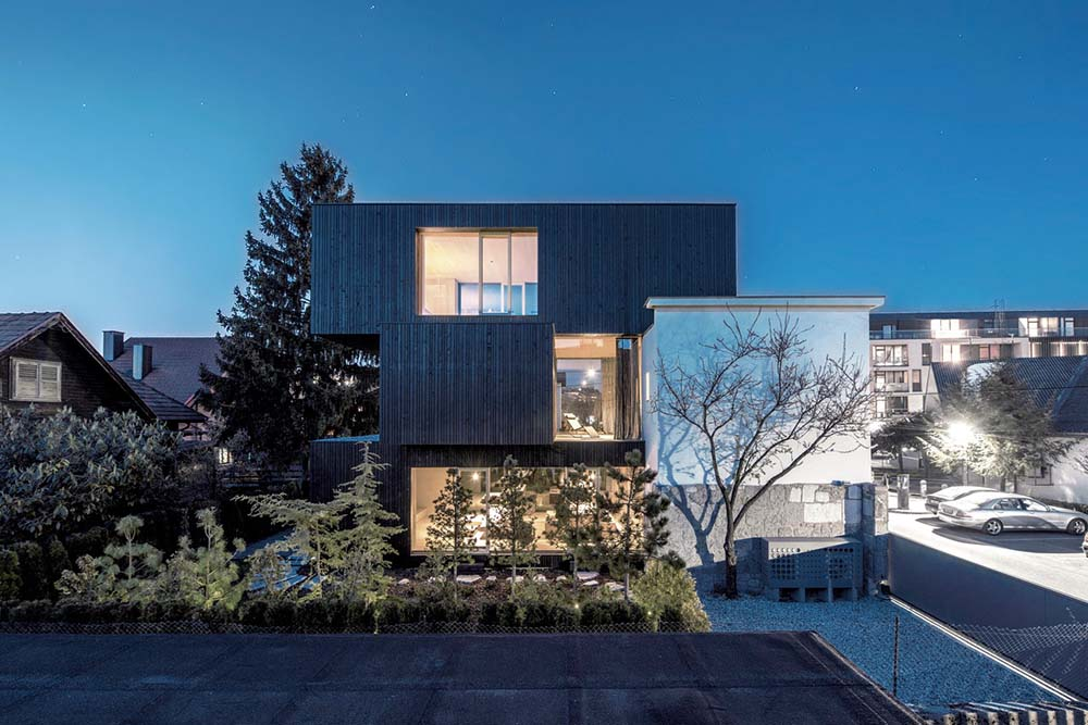 This is a view of the side of the house that showcases three box structures stacked on top of each other complemented by the glowing windows and landscaping of trees.
