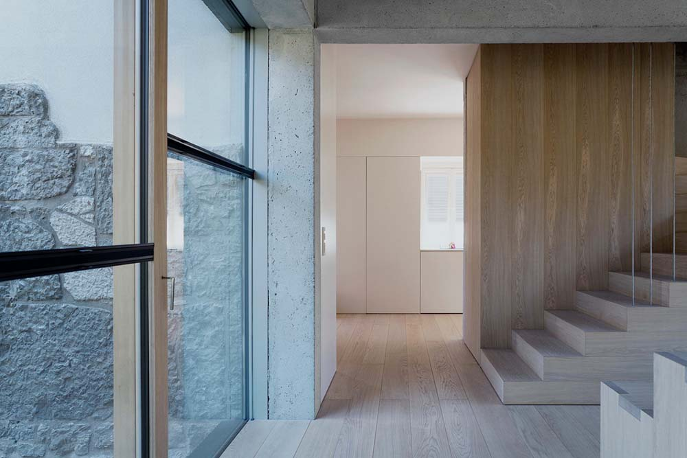 This bright area by the stairs is enlightened by the natural light of the glass wall.
