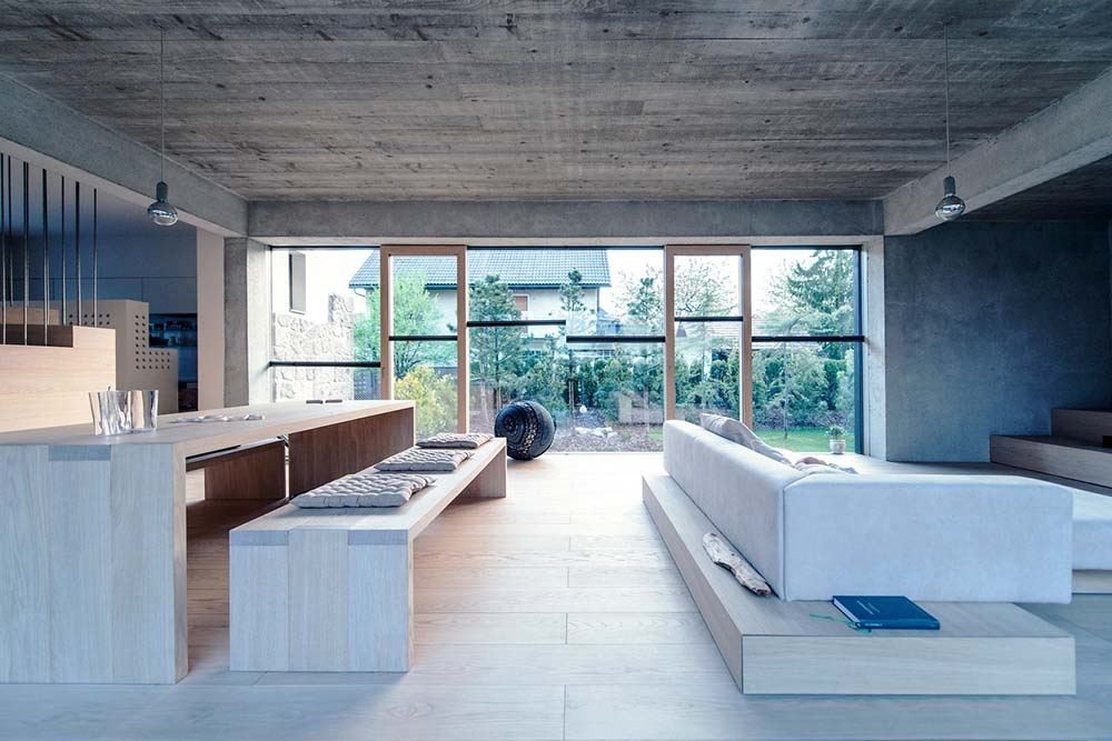 Behind the L-shaped sofa is the large wooden dining table paired with a couple of wooden benches with cushions.