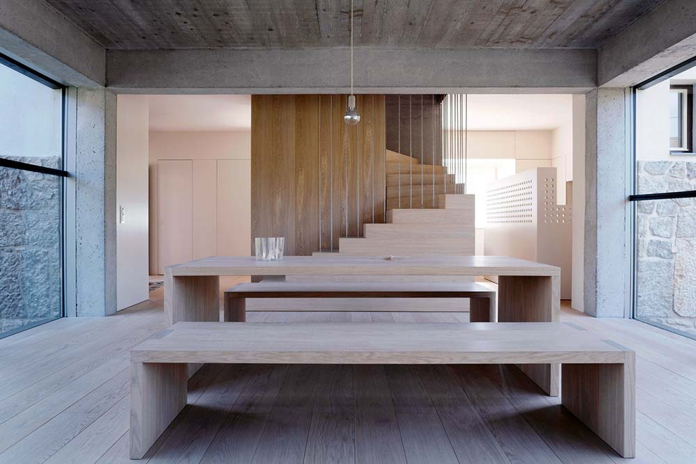 This is a closer look at the wooden rectangular dining table and benches that match the tone of the flooring.