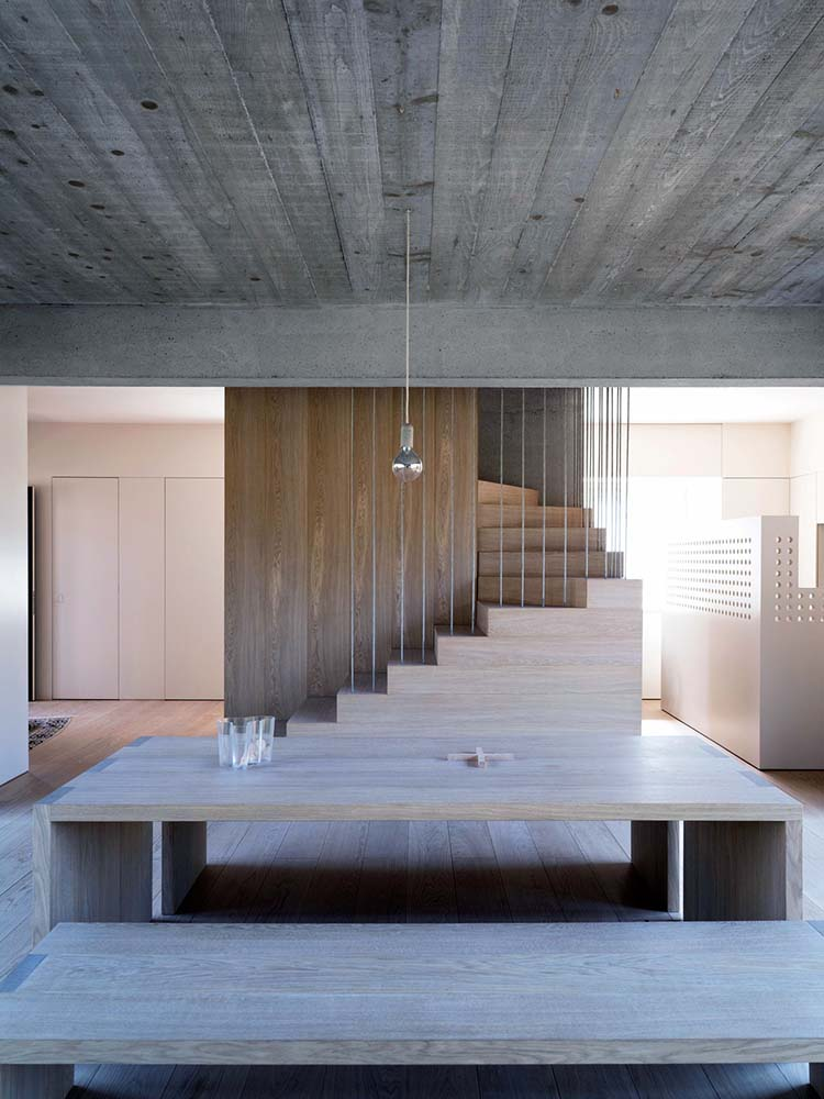 The wooden dining set also matches with the wooden steps of the staircase on the far side.