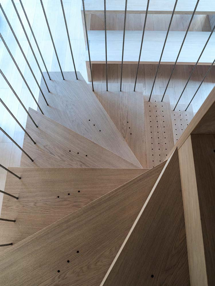 The wooden steps of the staircase is sided with thin railings.