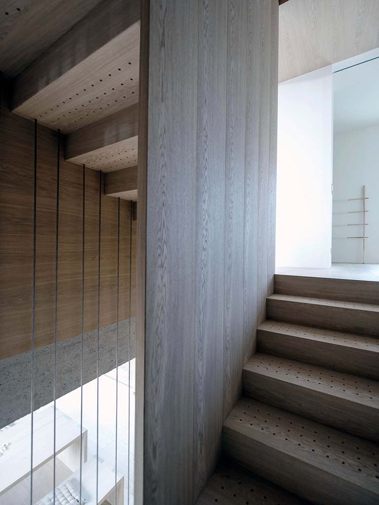 The wooden steps of the staircase with thin slats that connect to the ceiling.