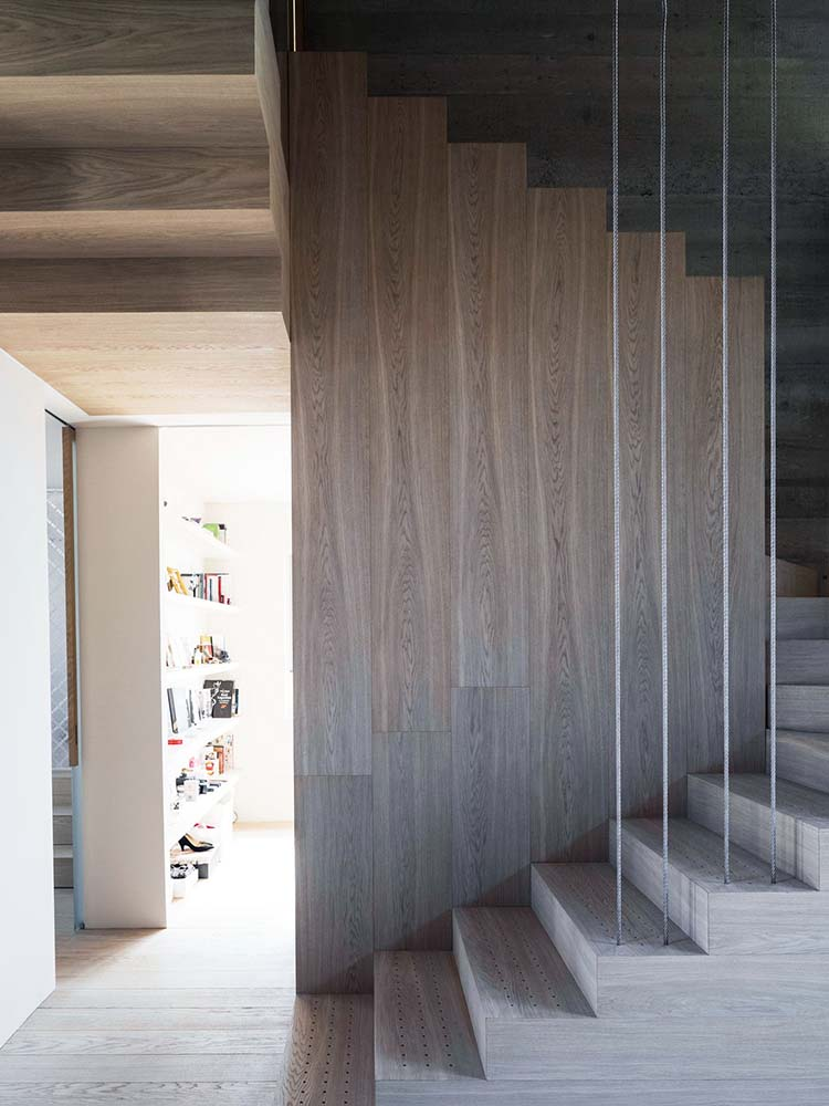 At the side of the staircase is a hallway with a large wooden open shelving on the side.