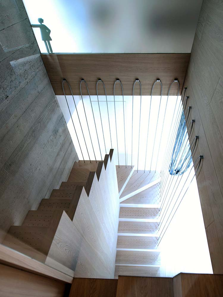 This is another look at the wooden staircase from the vantage of the second-levellanding.