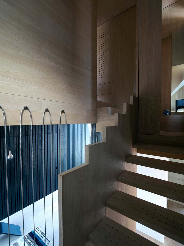 This angle of the wooden staircase showcases its design and simplicity paired with thin railings.