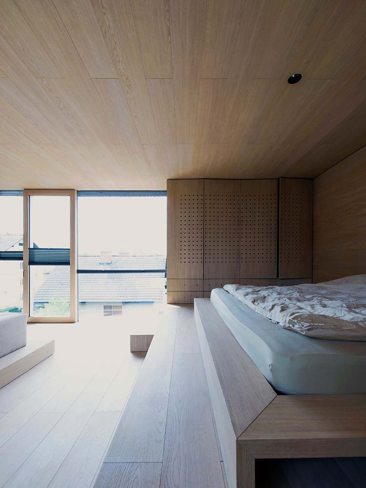 This is a closer look at the wooden platform of the bedroom area and a set of glass walls on the far side.