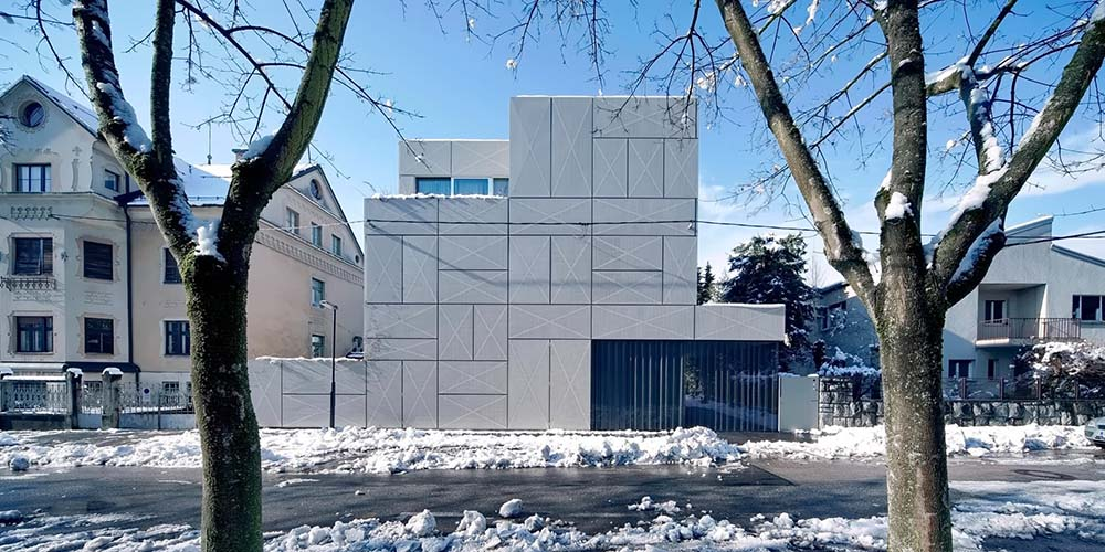 This is a look at the exterior of the house that has a minimalist design of concrete wall panels and glass giving the house a unique and simple look.