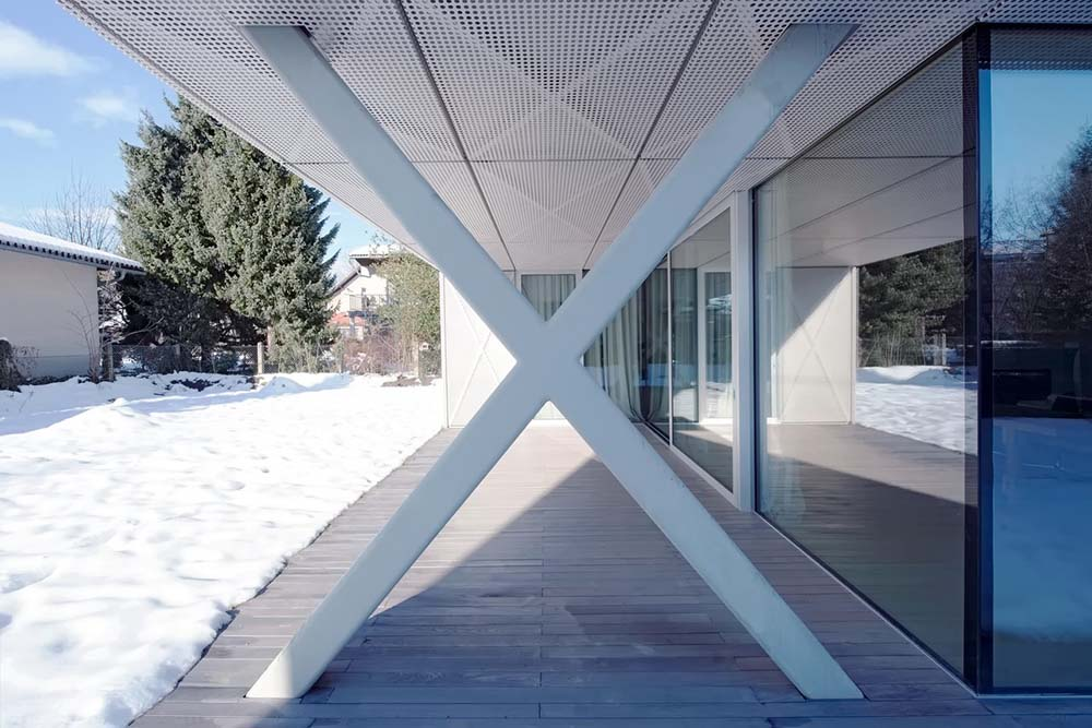 This is a close look at the covered patio of the house that has a ceiling supported by a cross structure.