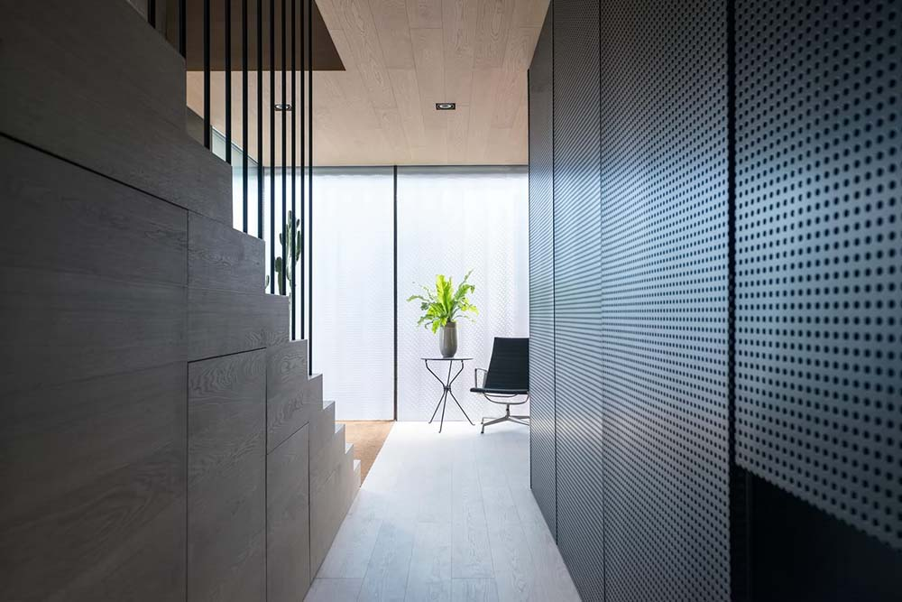 This is a view of the foyer from the vantage of the narrow hallway beside the staircase with a simple chair and side table.