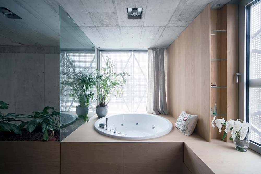 The bathroom has a large circular bathtub that is embedded into the large brown structure by the window adorned with a potted plant.