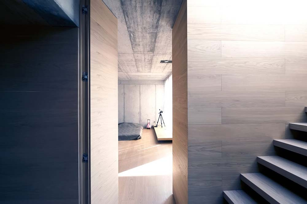 This is a look at the bedroom that has a wooden door that matches the wooden wall and the hardwood flooring of the bedroom that extends to the study area.