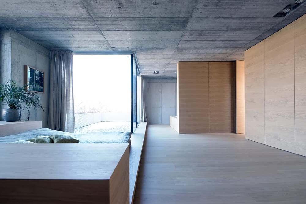 This is another view of the bedroom that has a large wooden platform bed. On the far side is the bathroom.