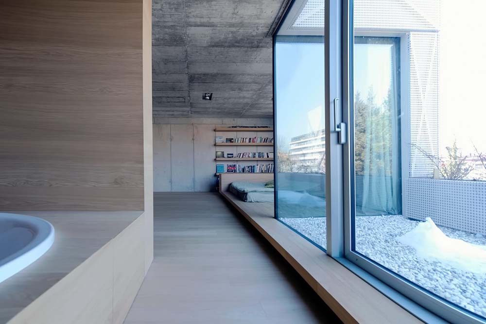 This is a closer look at the bathroom with a housed bathtub by the natural light of the glass house.