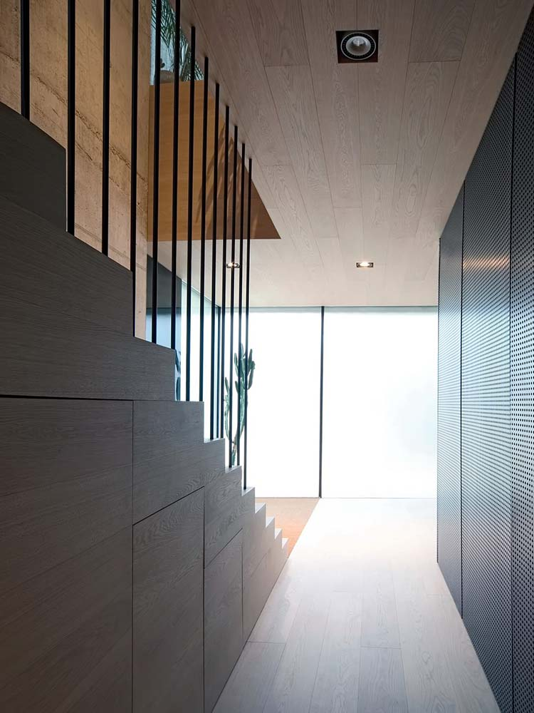 This is a look at the glass sliding doors opposite the staircase adorned with a potted plant on the corner.
