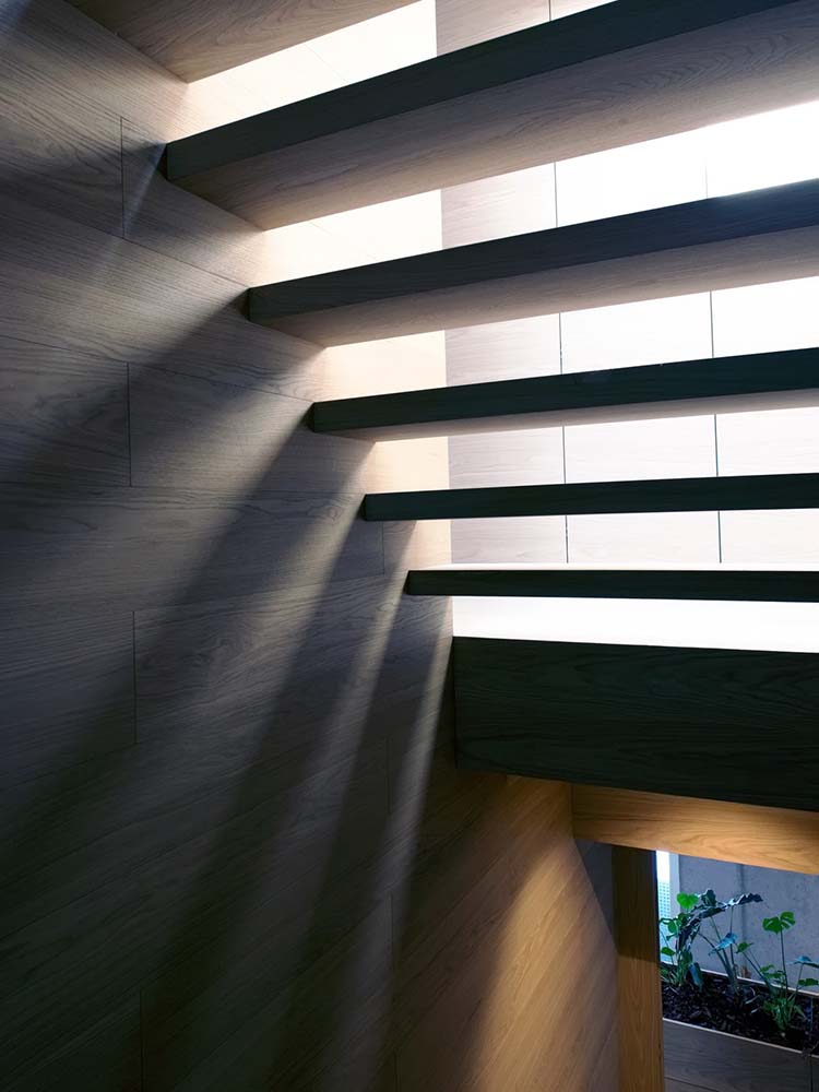This is a view under the stairs showcasing the warm light that passes through the spaces in between the steps.