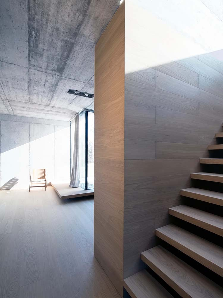 The tone of the walls pair well with the wooden steps of the staircase as well as the platform on the far side by the glass window.