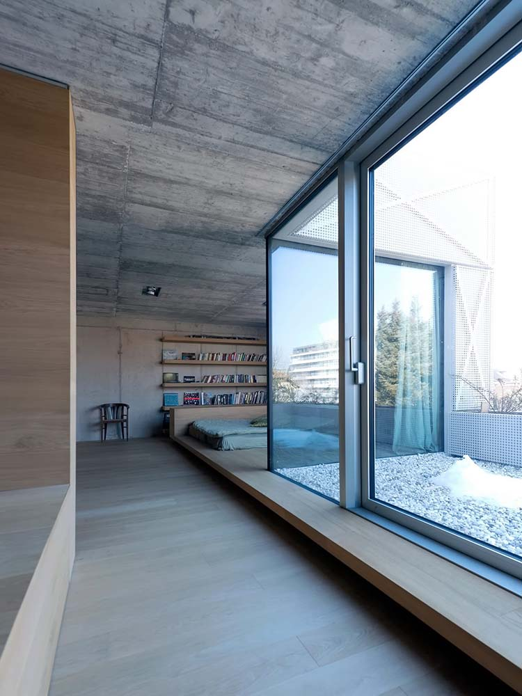 This is a view of the bedroom from the vantage of the bathroom area that has a housed bathtub across from the glass walls.
