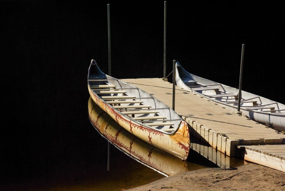 A couple of canoes docked at a riverside.