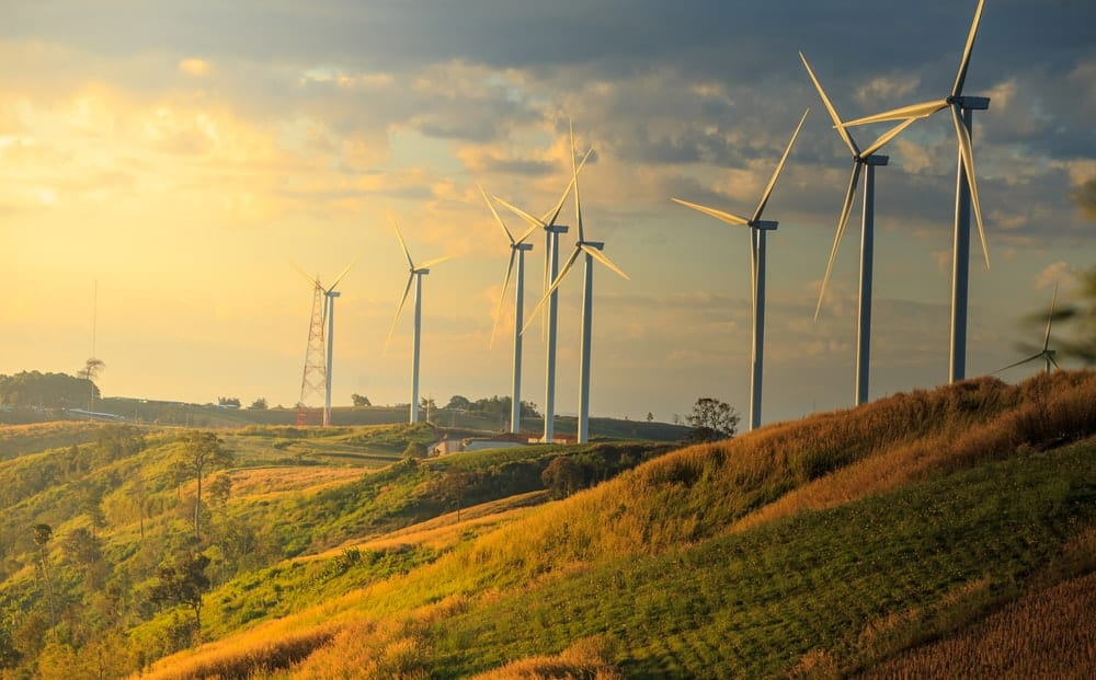 A row of wind turbines on a sunny morning.