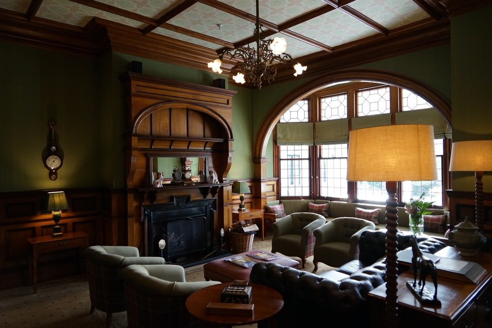 This is a living room inside a Queen Anne Victorian home with a fireplace, wooden panels and a large arched window.