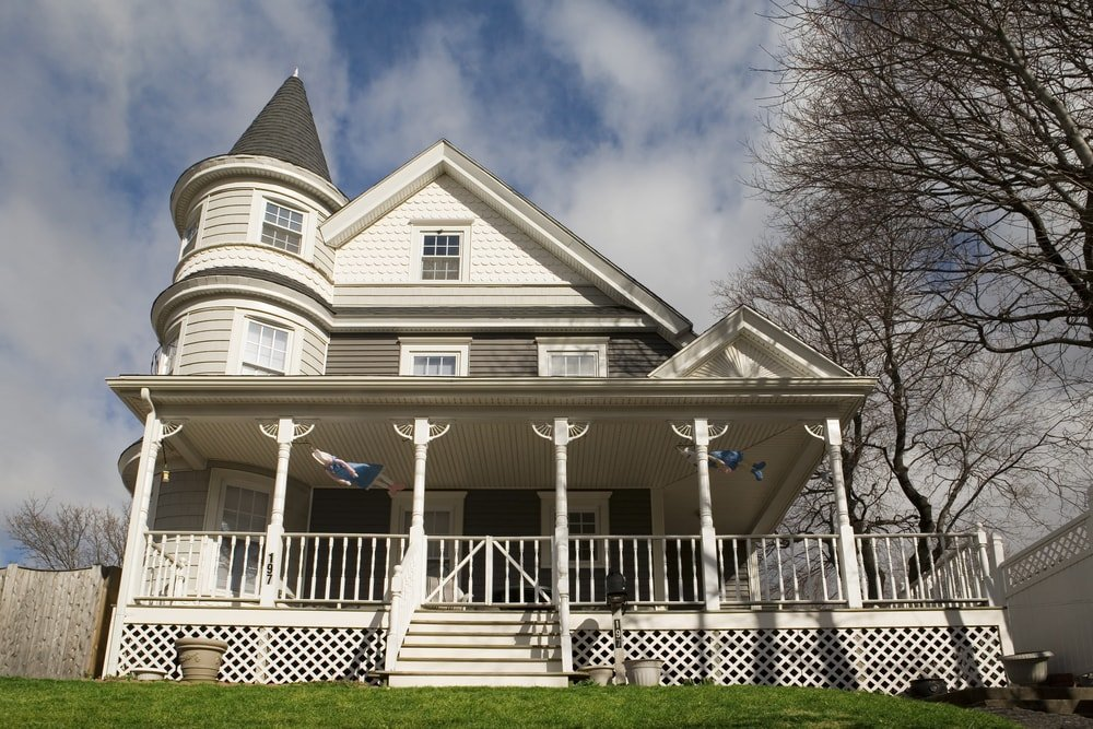 This is a bright beige Queen Anne Victorian home with wrap around porch and round tower.