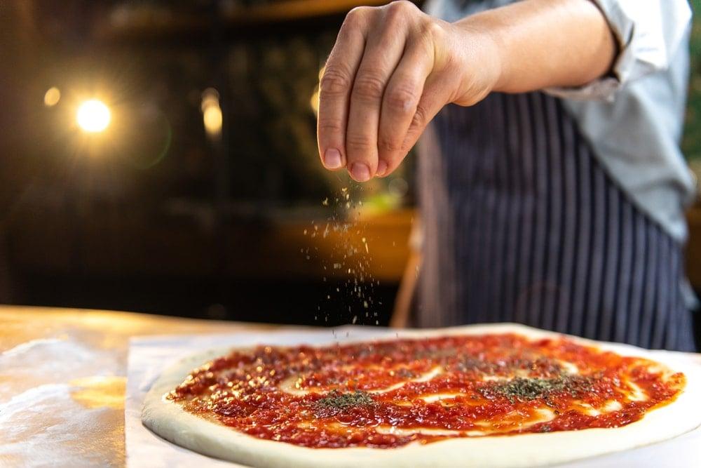 A chef sprinkling dried oregano on pizza.