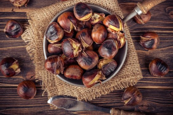 This is a close look at a bunch of roasted chestnuts on a rustic setup.