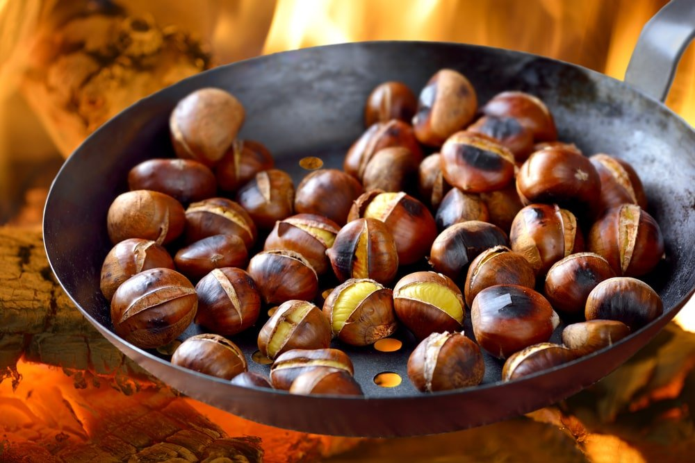 A bunch of chestnuts being roasted on an open fire.