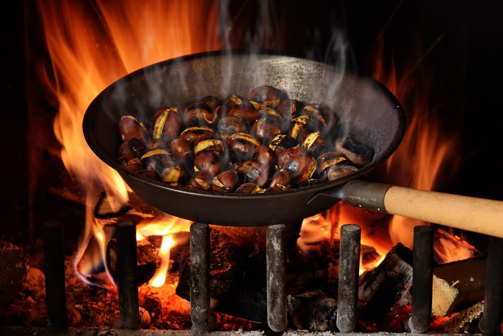 A pan of chestnuts being roasted over the open fire.