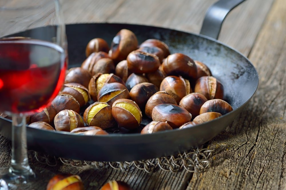 A pan of roasted chestnuts served with red wine on a wooden table.
