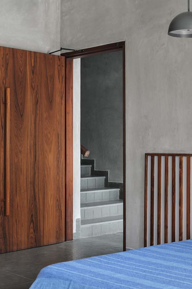 This is a look at the dark wooden door of the bedroom that stands out against the beige walls and flooring.