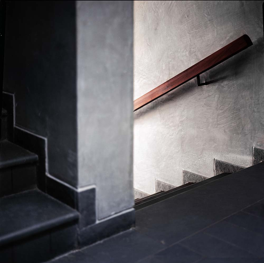 This is the staircase landing with dark gray flooring tiles and steps that contrast the light tone of the walls.