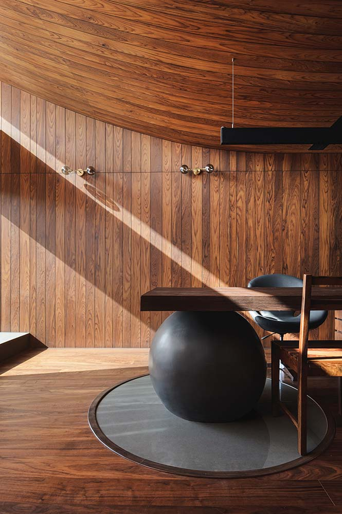 This side of the office showcases the large black ball support of the wooden desk. You can also the curvature of the wooden ceiling.