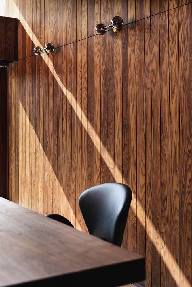 This is a closer look at the wooden paneled wall of the home office with modern lighting.