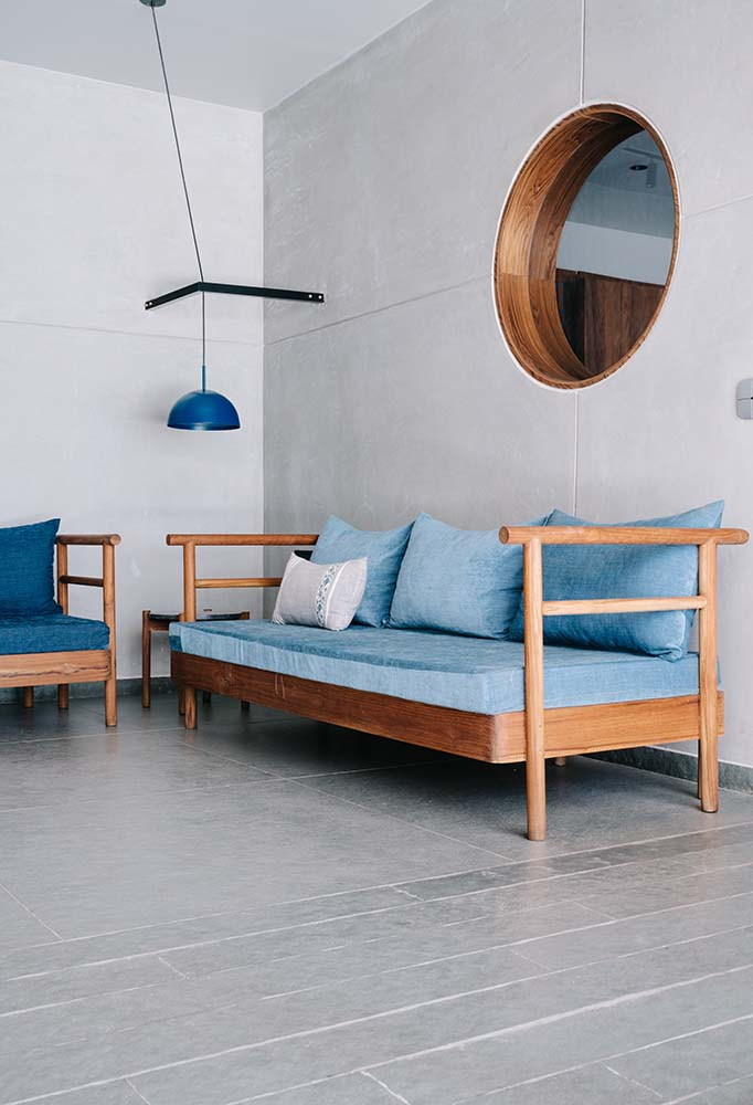The living room has a wooden cushioned sofa topped with a wall-mounted round mirror.