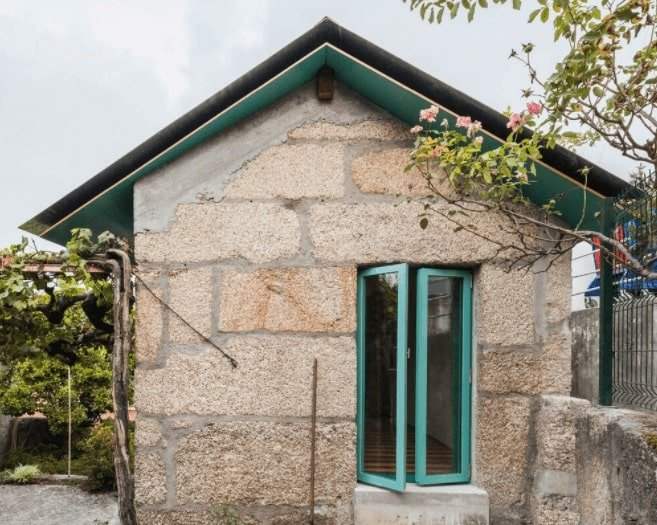 This is a small home with rustic and textured stone walls complemented by the colorful exterior accents and landscaping.