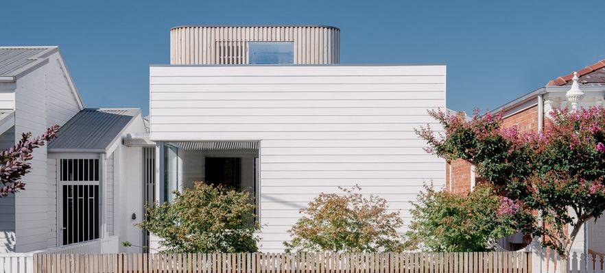 This is a front look at the white Beach-style house with bright white shiplap exterior walls and shrubs on the front yard behind a small fence.