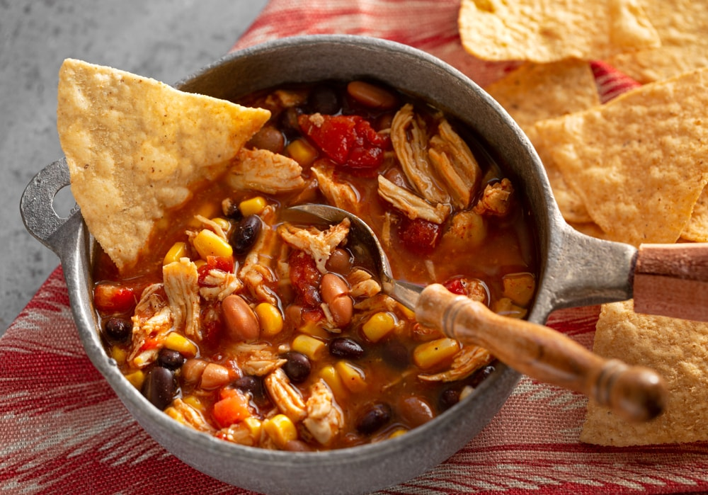 A pot of taco soup with a side of nachos.