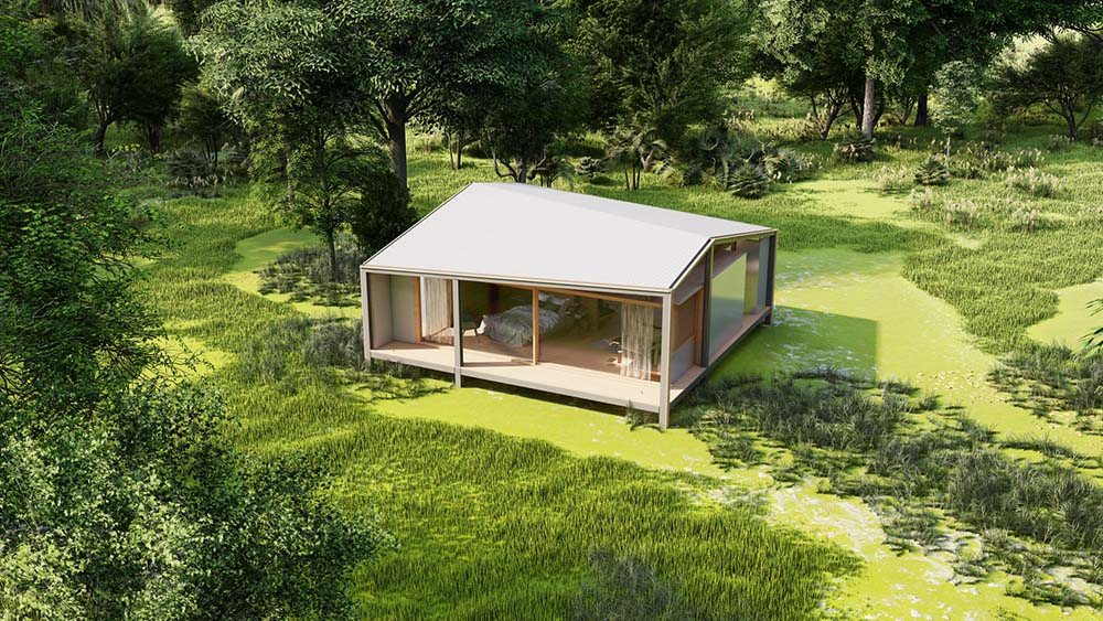 This is an aerial view of the tiny house and how it stands out against the surrounding green landscape of grass and tall trees.