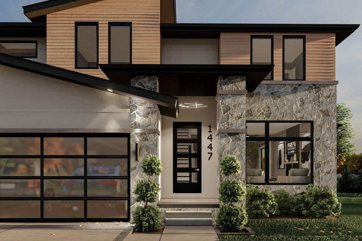 A closer look at the home entry showing the glass front door flanked by stone pillars.