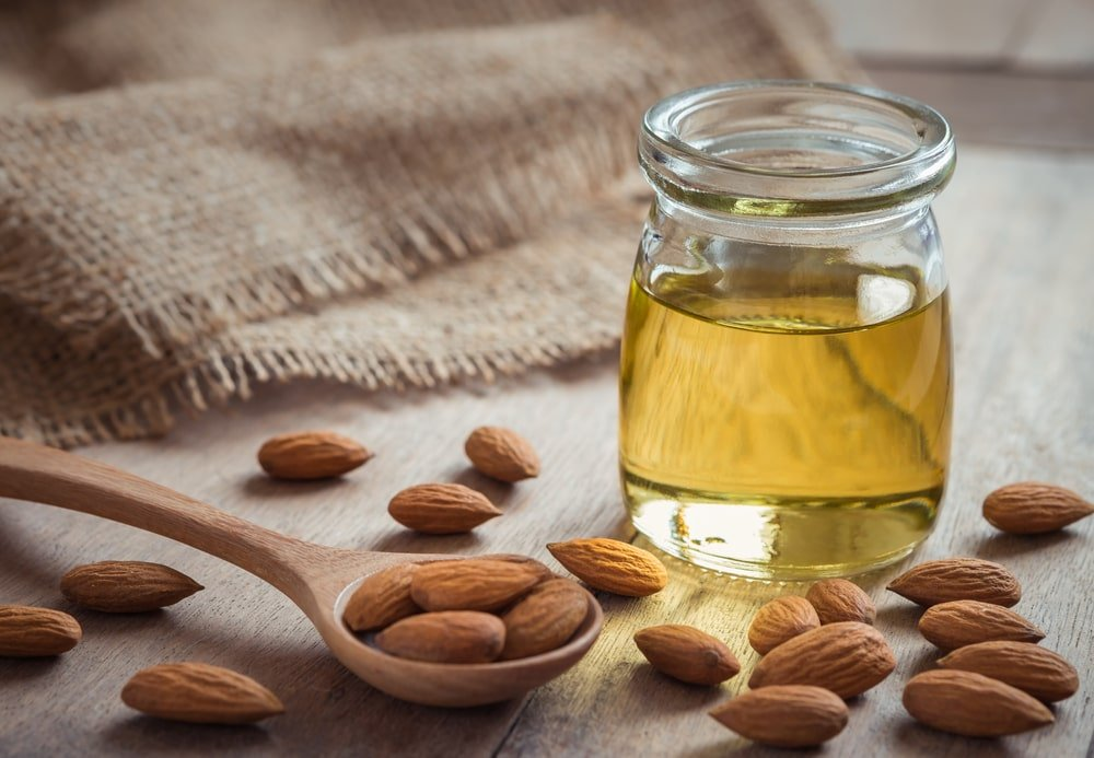 A spoonful of sweet almonds next to a jar of oil.