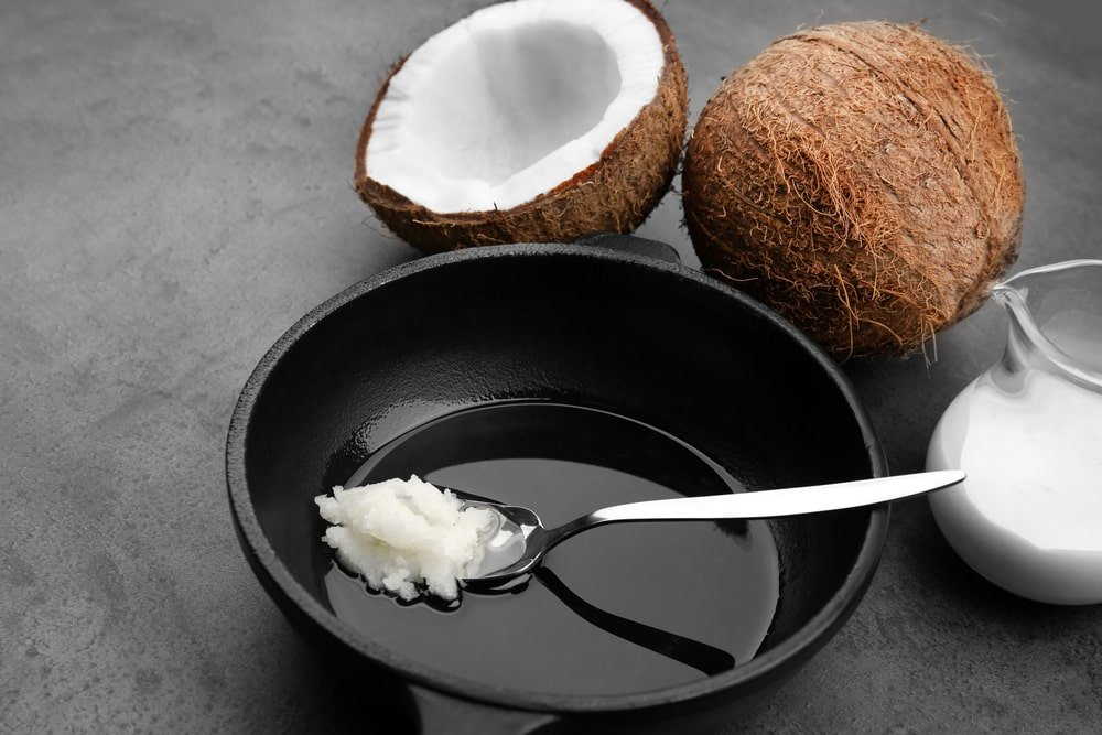 A pan with spoon and coconut oil.