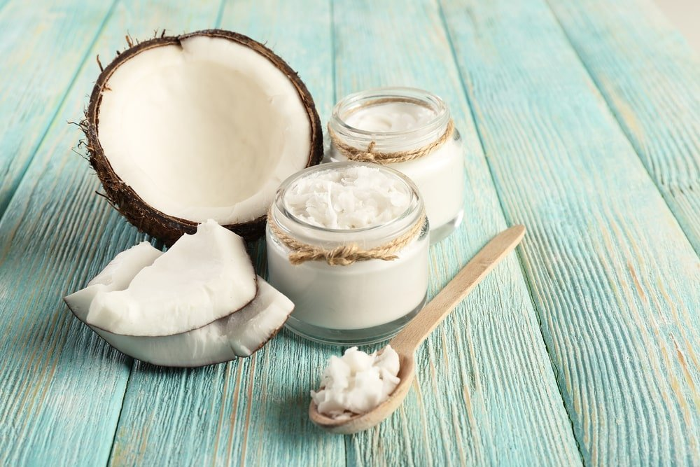 Fresh coconut oil in jars and wooden spoon.