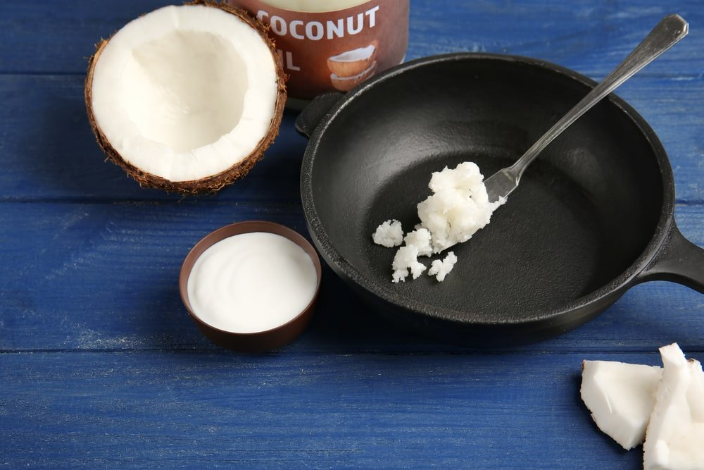 Putting fresh coconut oil on a frying pan.