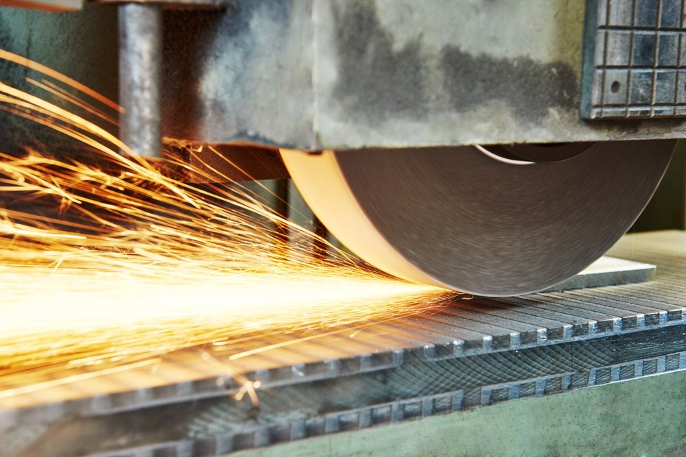A piece of metal being polished with a horizontal grinder.