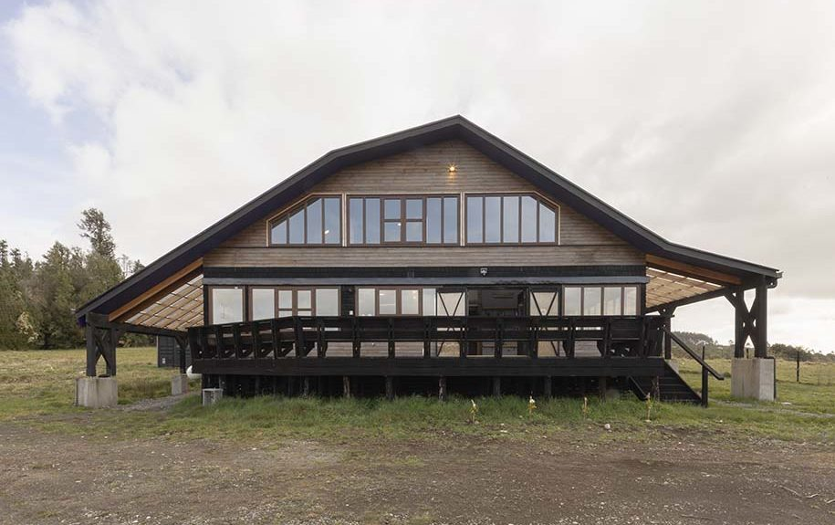 This is a front view of the house with a unique shape to its wide roof that is followed by the row of glass windows on the upper floor. The house also has a wrap-around porch and terrace with wooden railings.