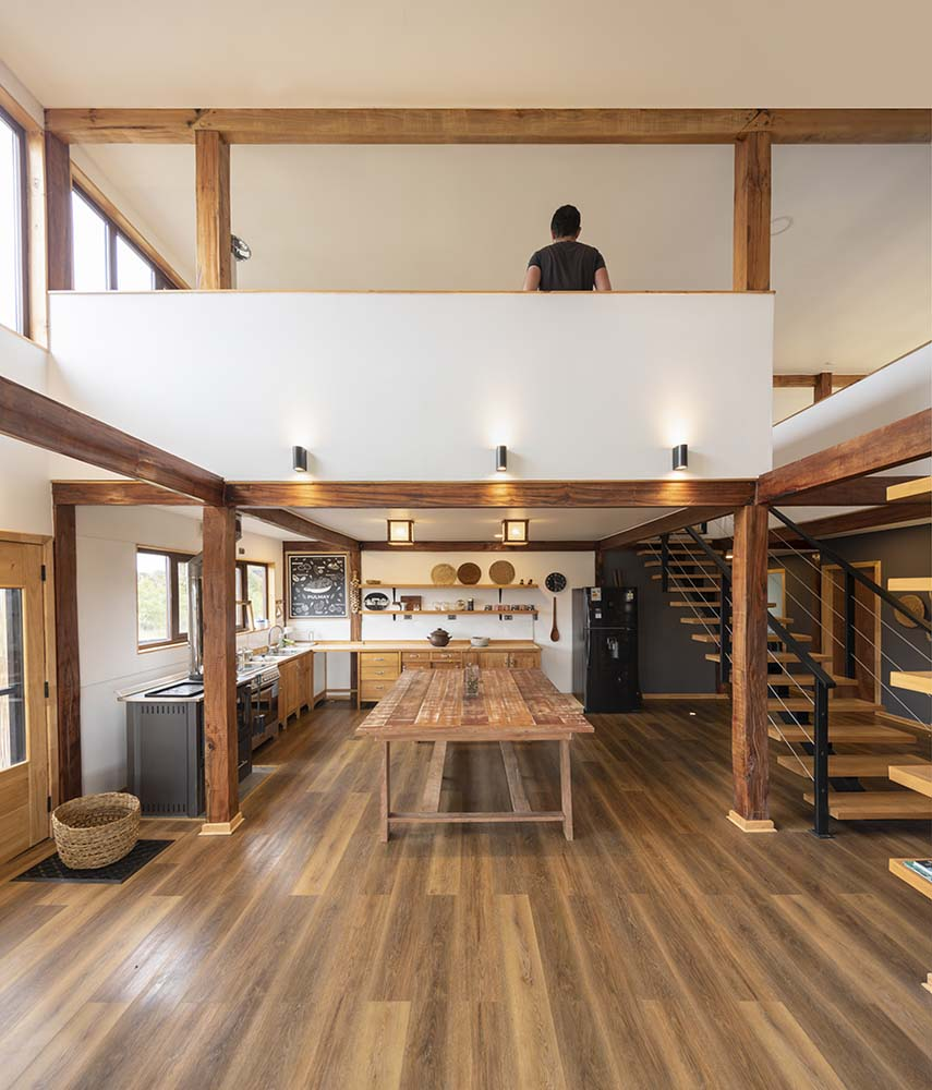 This is an interior view of the kitchen with a alrge wooden table in the middle serving as an island.