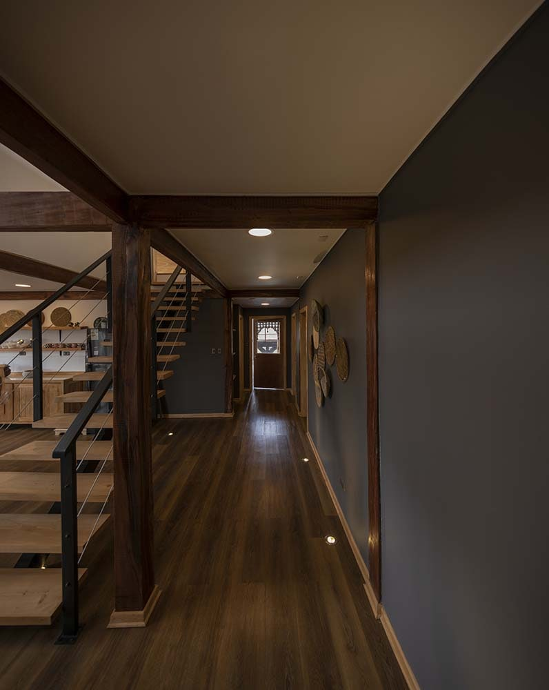 On the side of this staircase is a hallway with dark walls and dark hardwood flooring that pairs well with the wooden beams.